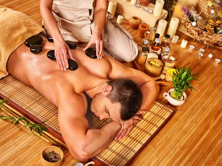 lastone therapy: Man getting stone therapy massage in bamboo spa. Lying on floor. Stock Photo