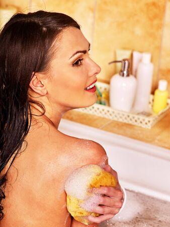 femme baignoire: Jeune femme de prendre un bain � bulles. Femme lavant son �paule. Banque d'images