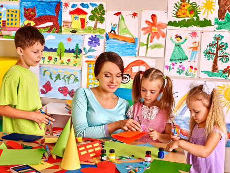 crafts person: Happy children  with scissors at classroom. Kids education.