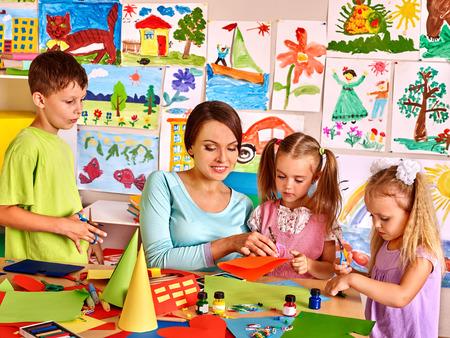maestra preescolar: Ni�os felices con tijeras en el sal�n de clases. La educaci�n de los ni�os. Foto de archivo