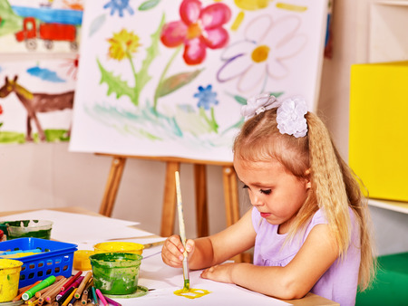 kids club: Child painting at easel in school. Kids pictures. Stock Photo