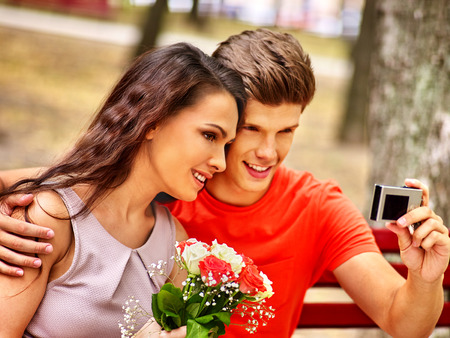 Couple with camera take pictures on bench. Selfie outdoor. photo