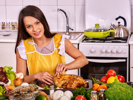 Happy young woman cooking chicken at home kitchen.