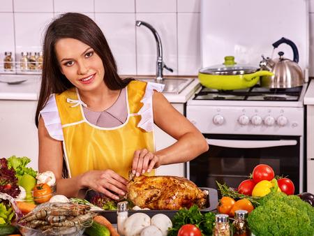 Glückliche junge Frau Kochen Huhn zu Hause Küche.