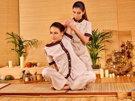 herbal massage ball: Young woman getting thai herbal massage ball. Girl sitting. Stock Photo