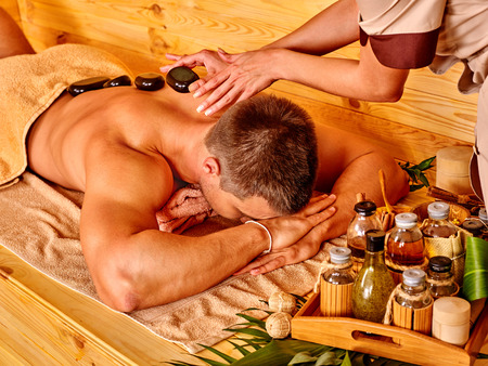 Man getting stone therapy massage in bamboo spa. Face is not visible.