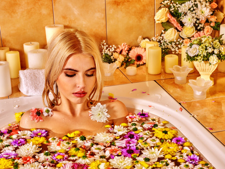 woman in bath: Woman relaxing at water spa. A lot of floweras