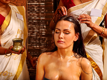 body oil: Young woman having head massage in ayurveda spa treatment. Stock Photo