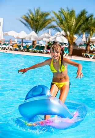 white beach: Little girl swimming on inflatable beach mattress. Stock Photo