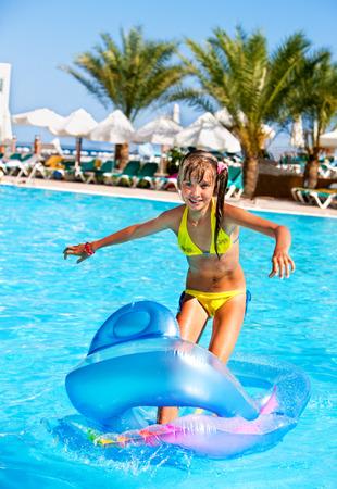 petite fille maillot de bain: Petite fille de natation sur matelas gonflable beach.