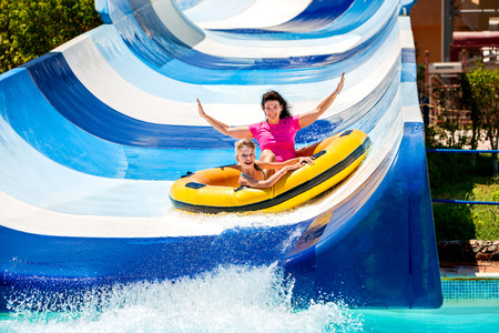 aqua park: Child with mother on water slide at aquapark. Summer holiday.