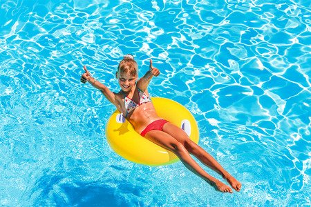 float tube: Happy child on inflatable ring in swimming pool. Stock Photo