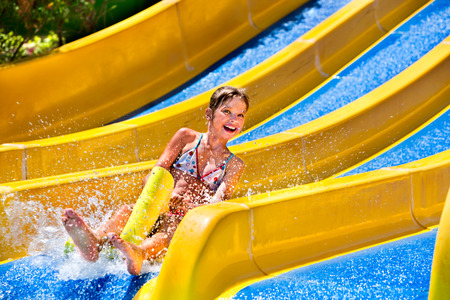 little girl child: Children on water slide at aquapark. Summer holiday. Stock Photo