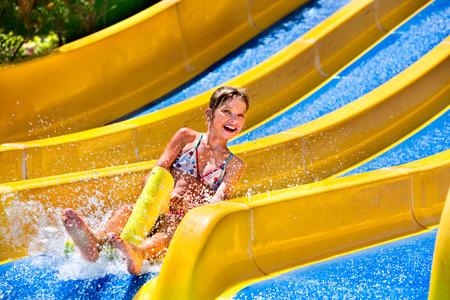 ni�o corriendo: Los ni�os en tobog�n de agua en parque acu�tico. Vacaciones de verano. Foto de archivo