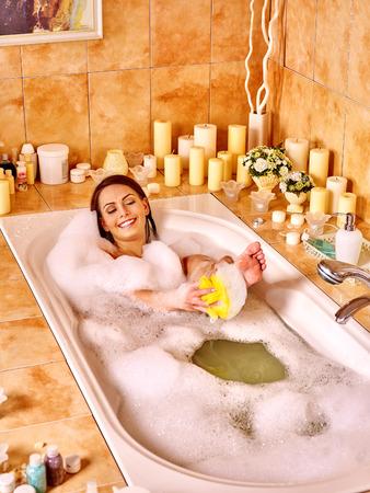 lying in bathtub: Young woman wash leg in bathtube.