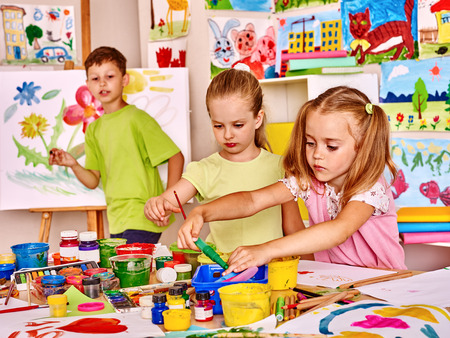 Child painting at easel in school. Teacher help.