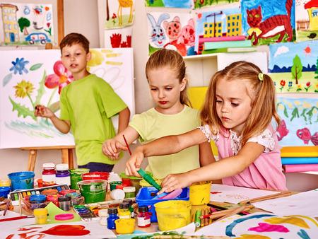 peinture pour enfants au chevalet à l'école. aide des enseignants.