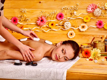 stone therapy: Woman getting stone therapy massage in wooden spa. Stock Photo