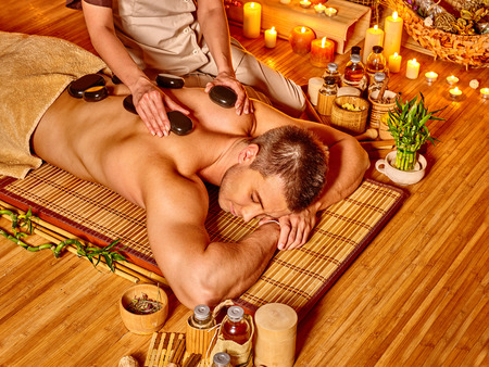 lastone: Man getting stone therapy massage in bamboo spa.