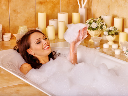 Femme de détente sur l'eau dans le bain moussant.