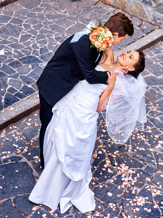 Groom carries his bride over back. Outdoor. photo