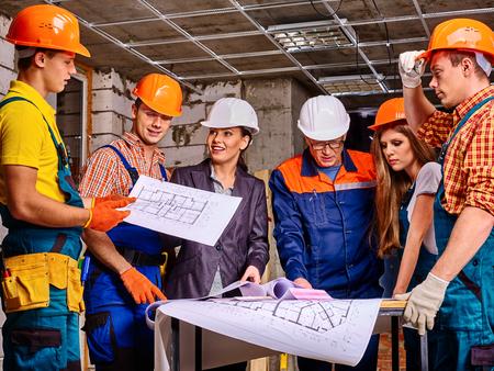 builder: Business group people in builder helmet indoor.