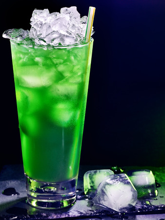 pilsner glass: Green drink  with cube ice and mint leaf on dark background 34