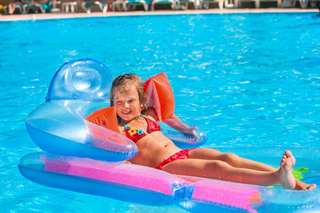 armbands: Little girl swimming on inflatable beach mattress. Armbands on hand
