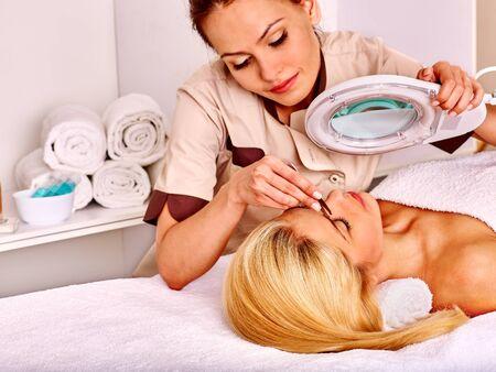 tweezing: Woman getting tweezing eyebrow by beautician. Indoor. Stock Photo