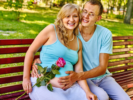 enceinte: Pregnant woman, holding flower with man  outdoor in park. Hand on belly
