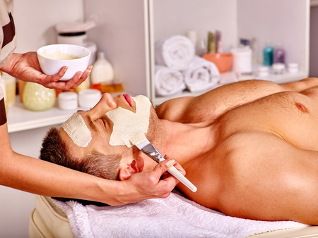 Man with clay facial mask in beauty spa. Make up brush.