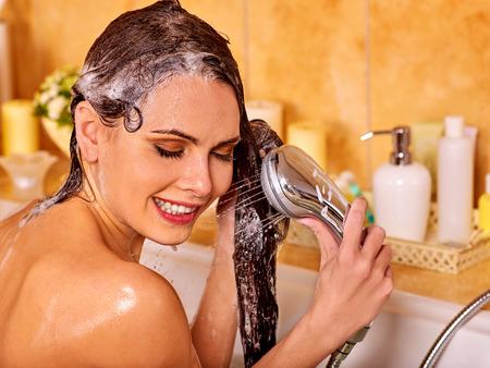 mujer bañandose: La mujer lava su cabeza al baño casa. La humectación del cabello.