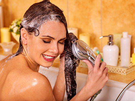 Woman washes her head at home bathroom. Wetting hair. Stock Photo