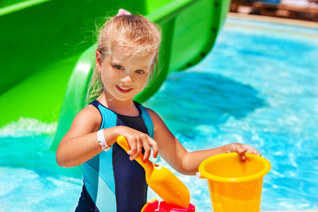 kids wear: Child with bucket in swimming pool.  Summer outdoor. Yellow and blue.