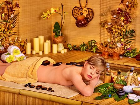 stone therapy: Woman getting stone therapy massage in bamboo spa. A lot of flower and candle. Stock Photo