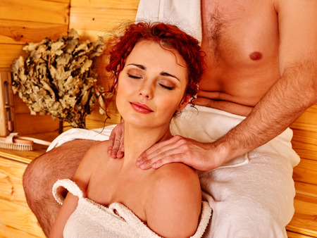 Couple man and woman    relaxing at sauna. Man does girl massage. Stock Photo