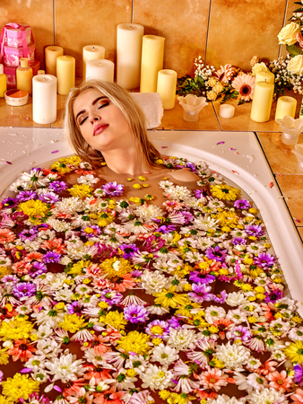 aqueous: Woman relaxing at water spa. Aqueous surface covers a lot of colored flower heads.