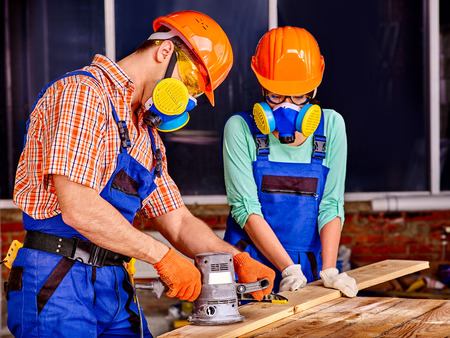 Man and woman in builder helmet with electric planer. Stock Photo