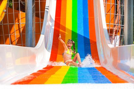 smiling child: Happy child girl in bikini sliding water park. Gesture thumb up. Stock Photo