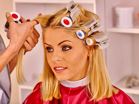 hot rollers: Happy woman wear hair curlers on head in barbershop. Stock Photo