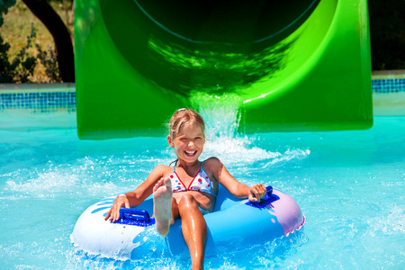 child in bikini: Child on water slide at aquapark. Summer holiday. Green and blue. Stock Photo
