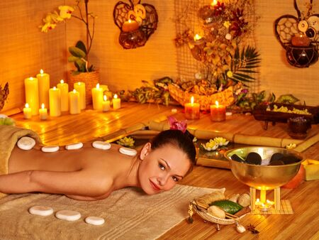 stone therapy: Woman getting a lot of white stone therapy massage in oriental spa.
