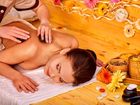 stone therapy: Happy woman getting stone therapy massage in gerbera spa.