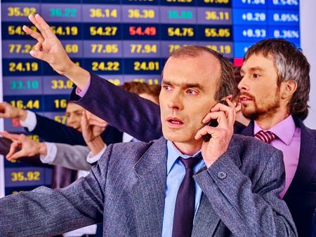 bursatil: Hombres de negocios Grupo con el tablero de bolsa de valores en la oficina. Hombre en primer plano. Foto de archivo