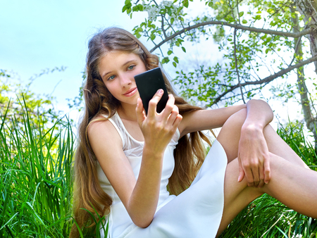 Girl do selfie near  blossoming cherry tree on  phone outdoor. Romantic style.