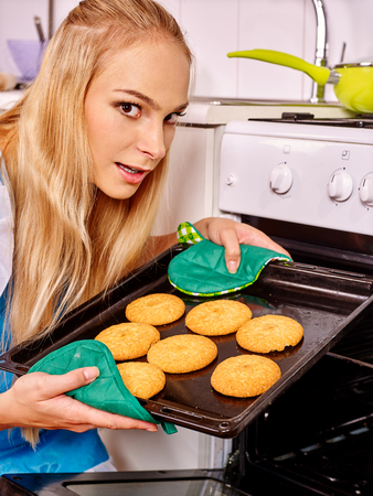 woman baking: Young woman baking  cookies at ktchen.