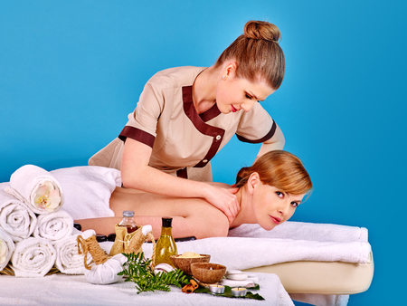 lastone: Young woman getting spa lastone therapy outdoor. Blue background.