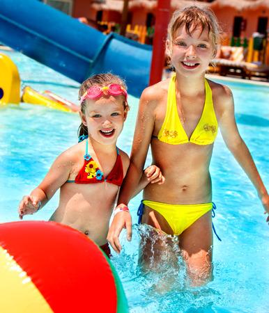 water play: Little girl  in bikini playing ball in swimming pool.