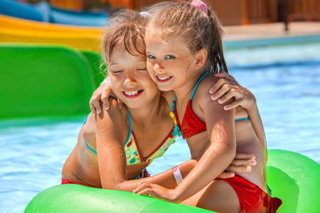 one piece: Two children sitting on green inflatable ring in swimming pool. Stock Photo