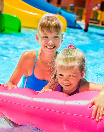 float tube: Female children sitting on pink inflatable ring in swimming pool.